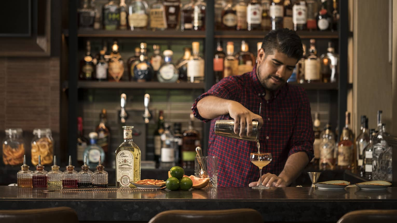Bartender wearing red checkered shirt pours cocktail at dark bar by liquor display