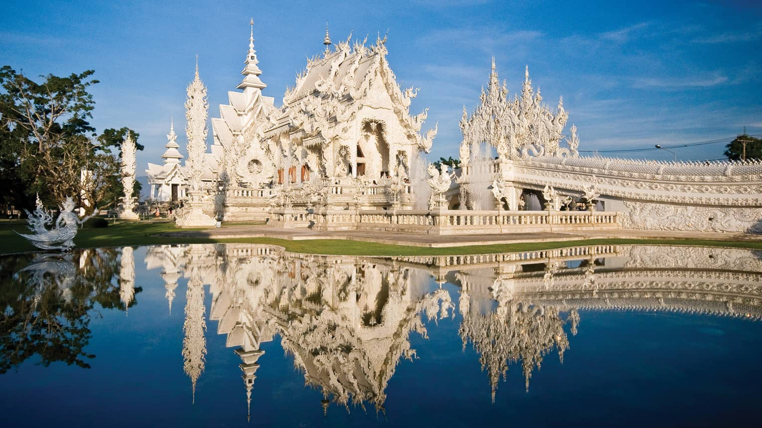 An ornate white castle reflecting in a pond