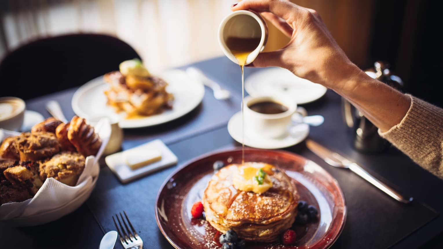 Close-up of hand pouring syrup over stack of pancakes on dining table by pastry basket, coffee