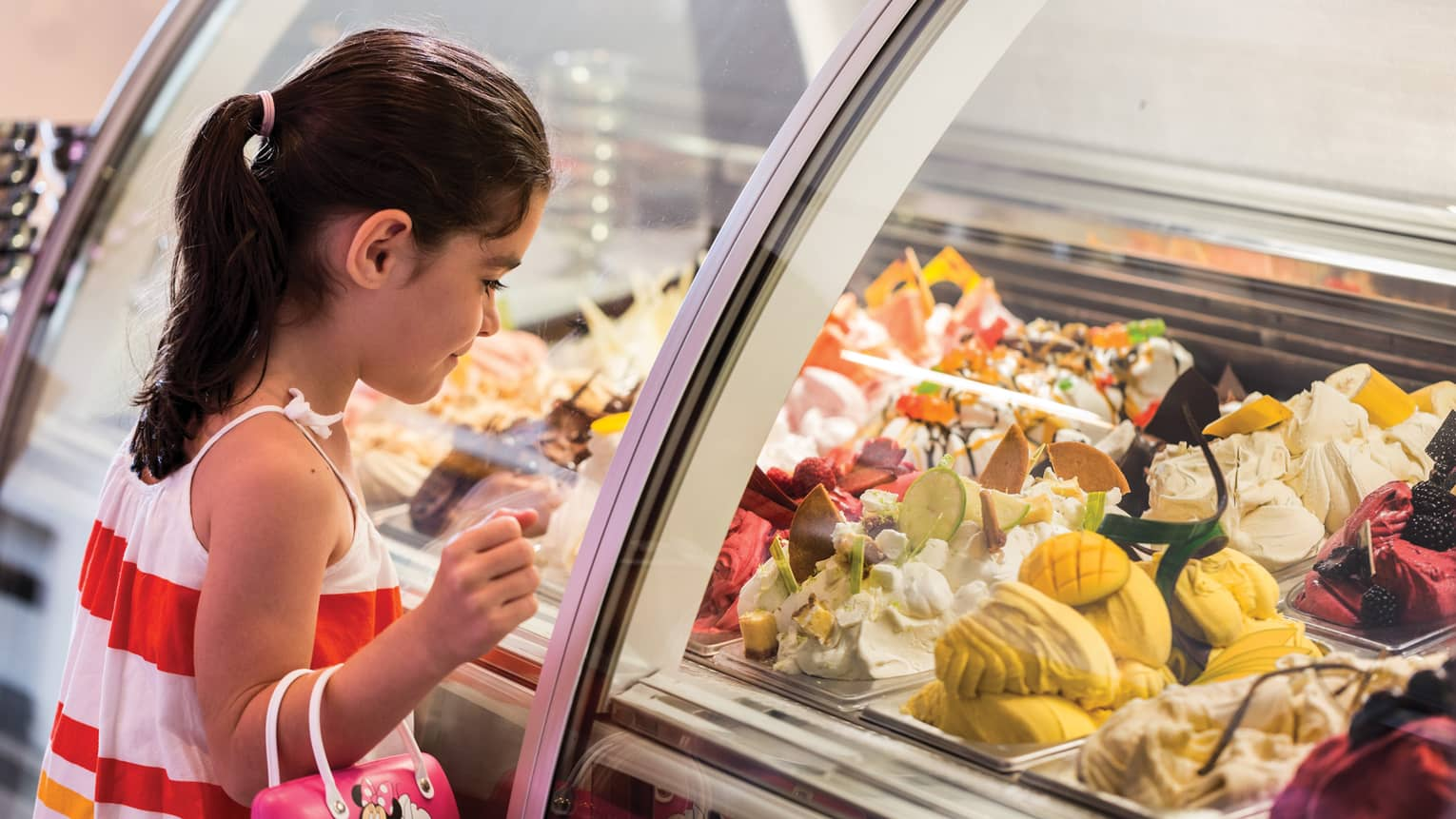Girl stands at Lickety Split glass counter, looks in at gelato flavours on display
