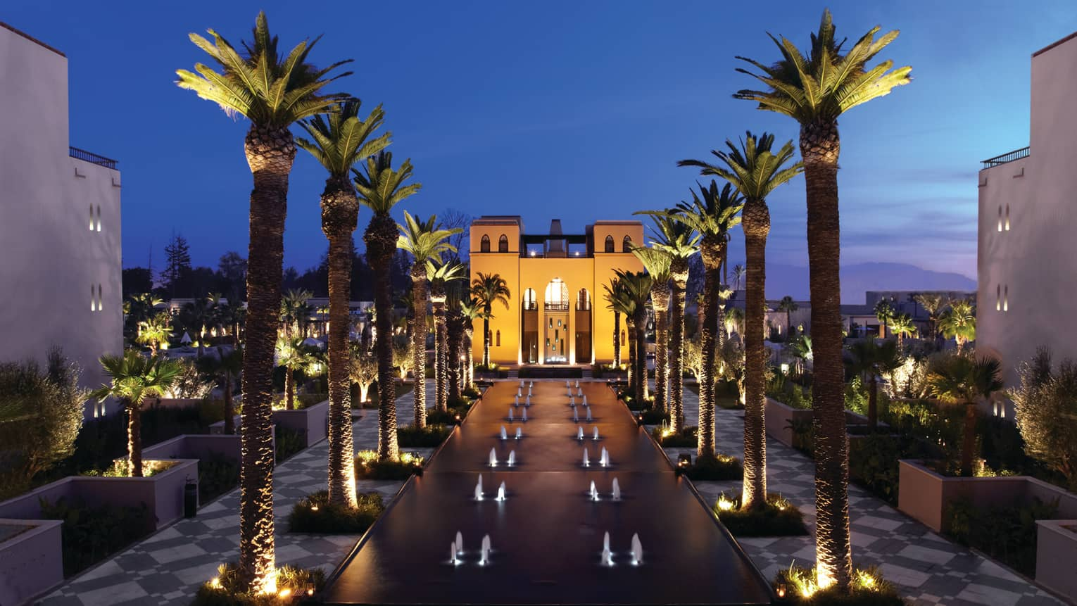 Fountains between rows of tall palm trees in front of illuminated Four Seasons Resort Marrakech hotel at night