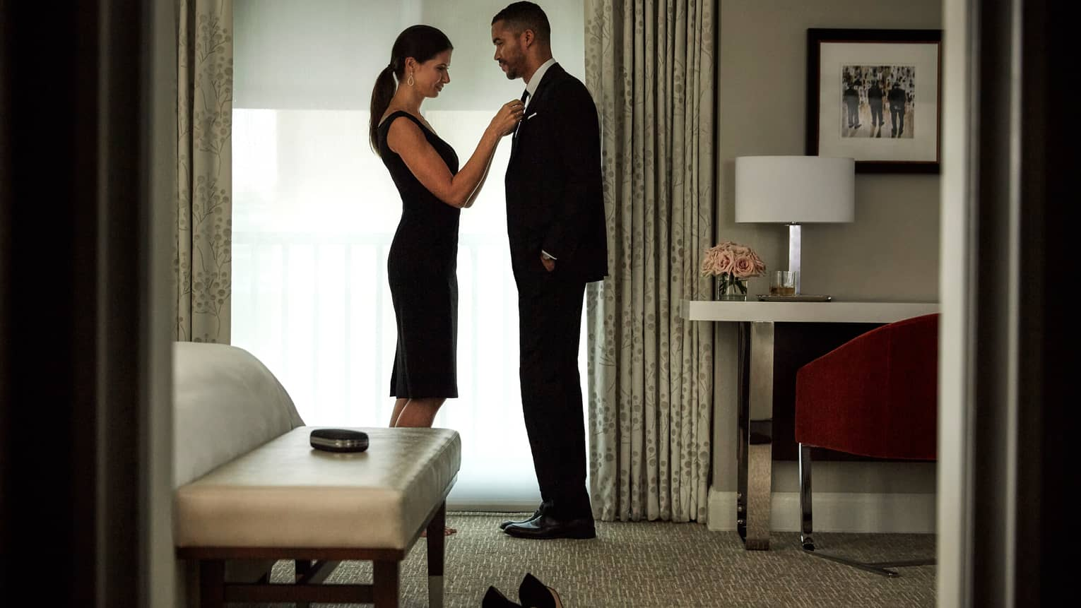 Woman in black dress fixes tie for man in suit by hotel room window with white shades, work desk and bench