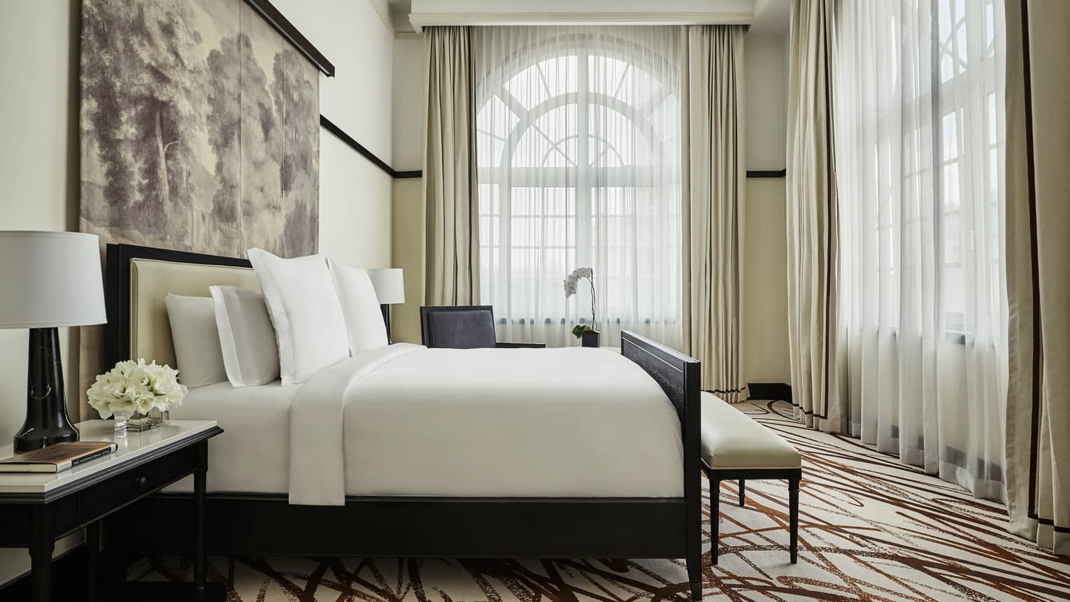 Governor's Suite bedroom, crisp white decor, sunny, arched corner windows with sheer curtains