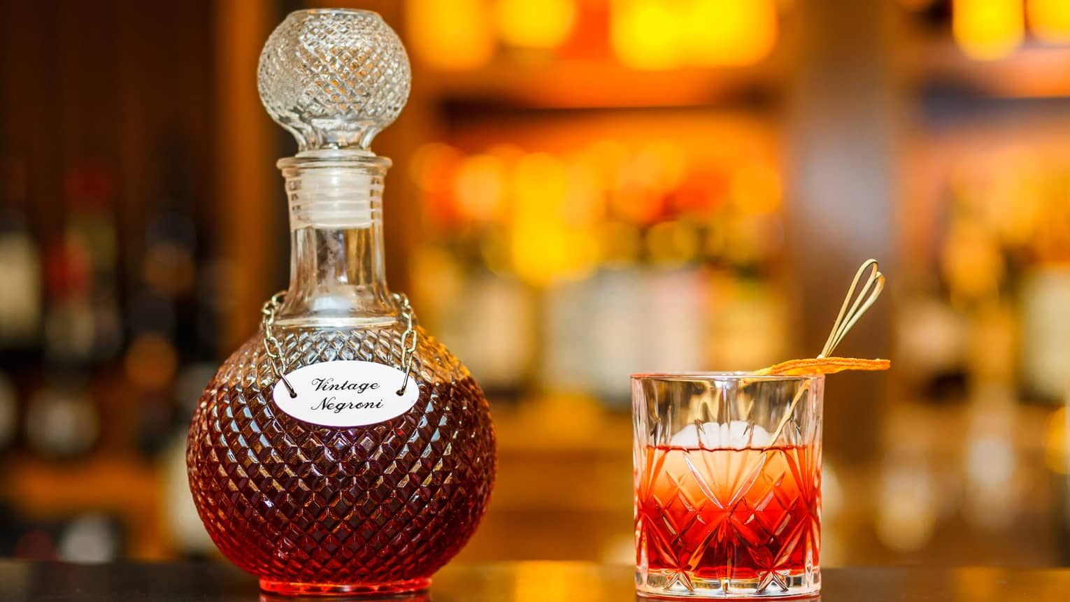 Vintage Negroni liquor in crystal bottle beside cocktail in rock glass