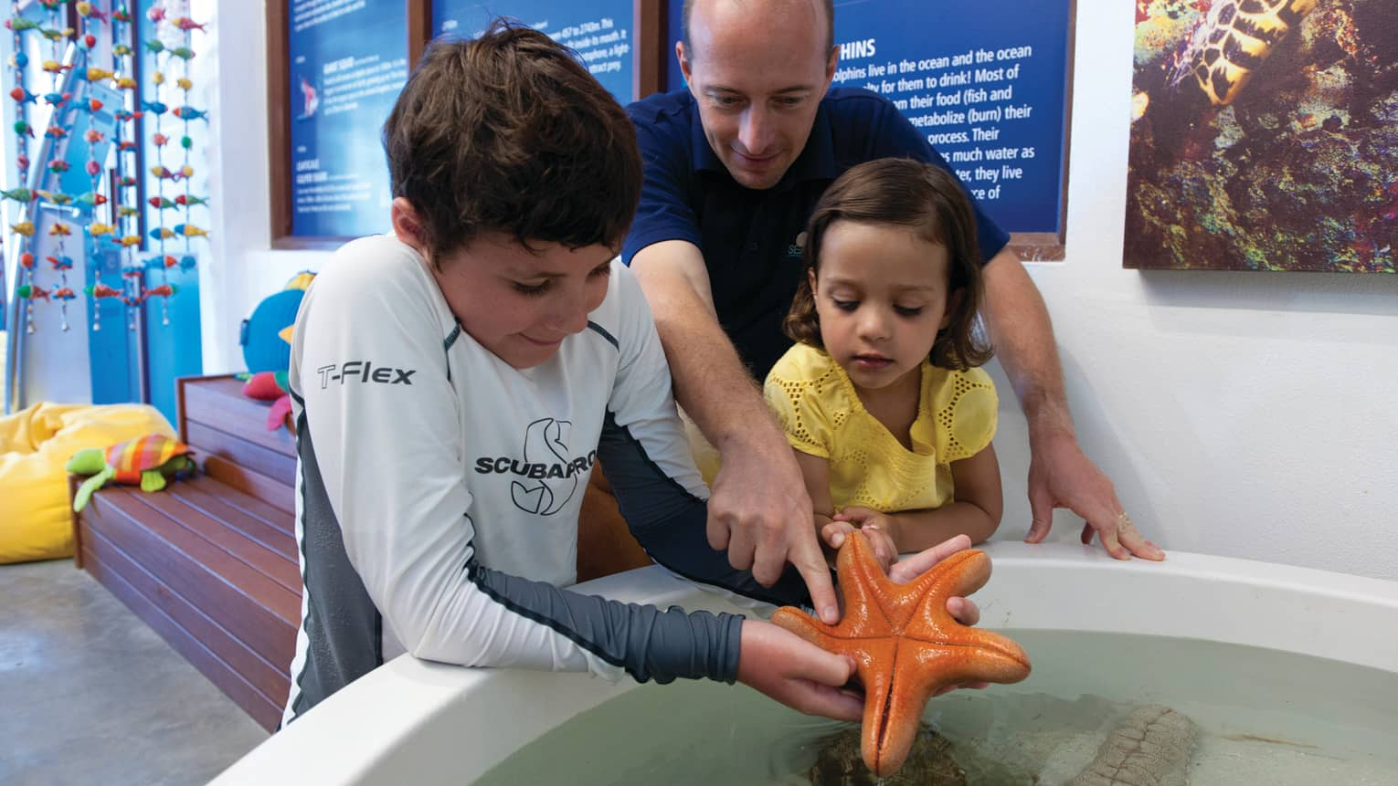 Man, young boy, girl examine large starfish in Marine Discovery Centre