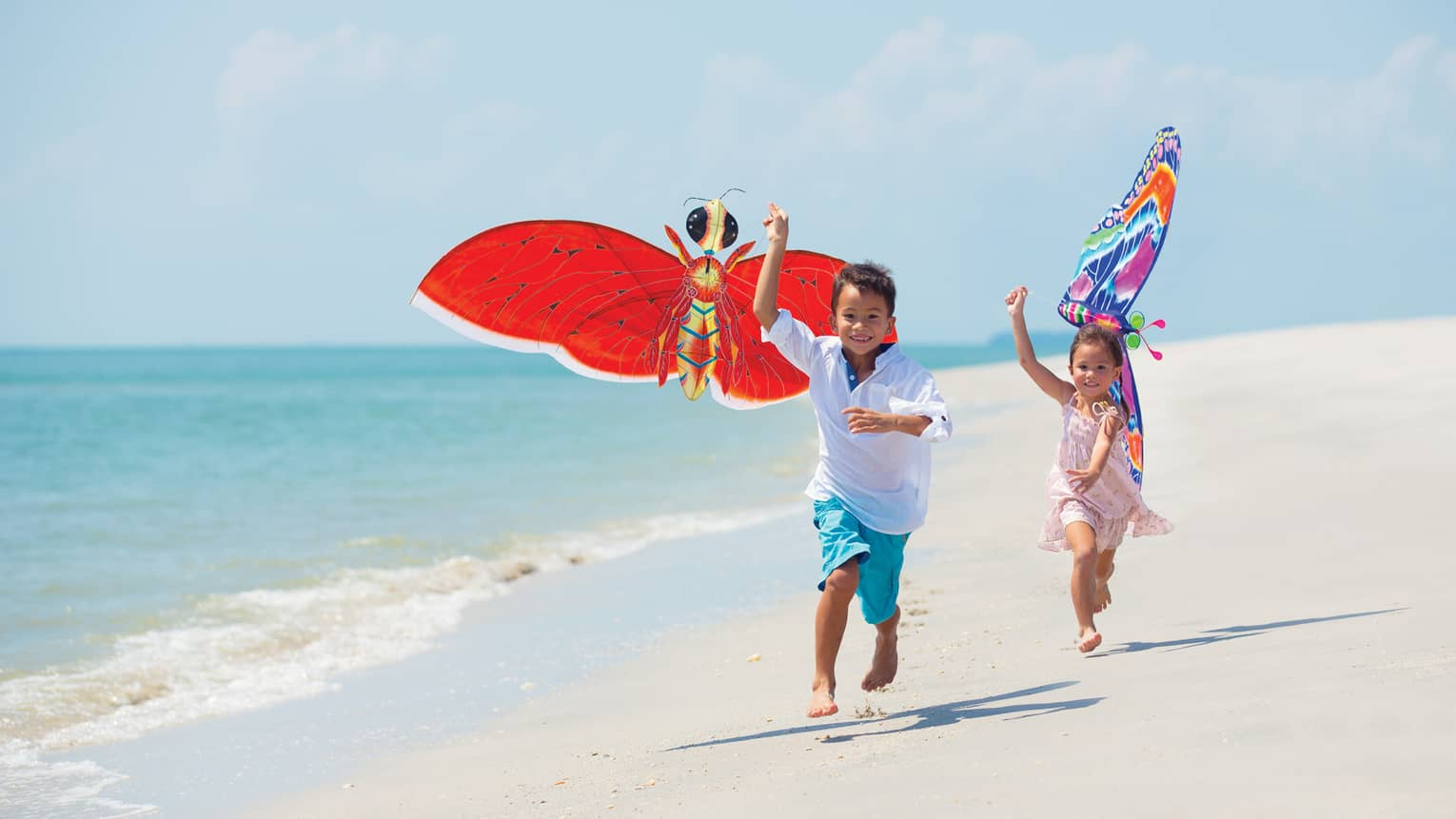 Two young children run with colourful butterfly kites on white sand beach