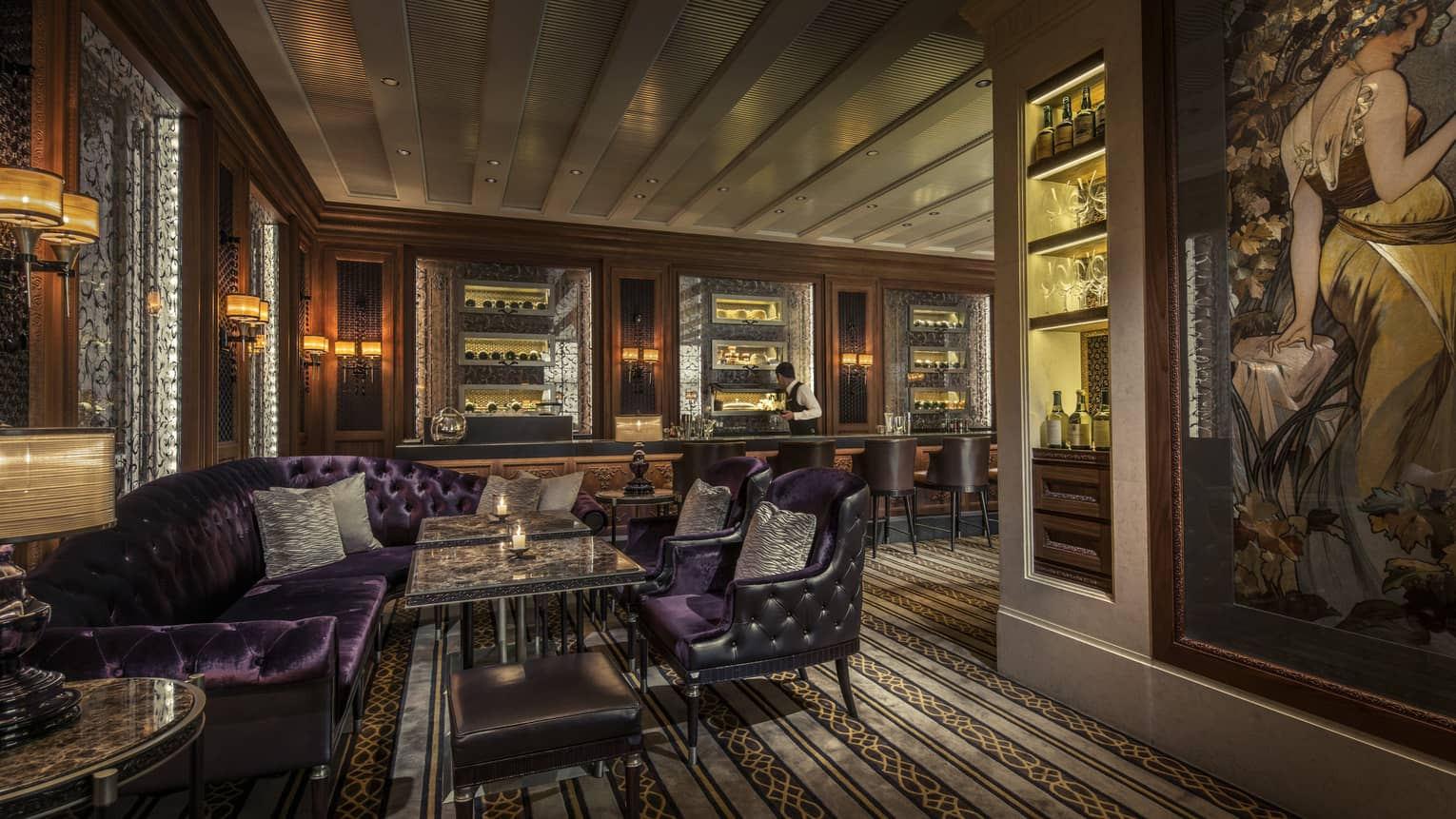Dimly-lit Caprice Bar lounge with velvet purple sofas, leather armchairs, liquor on shelves with light