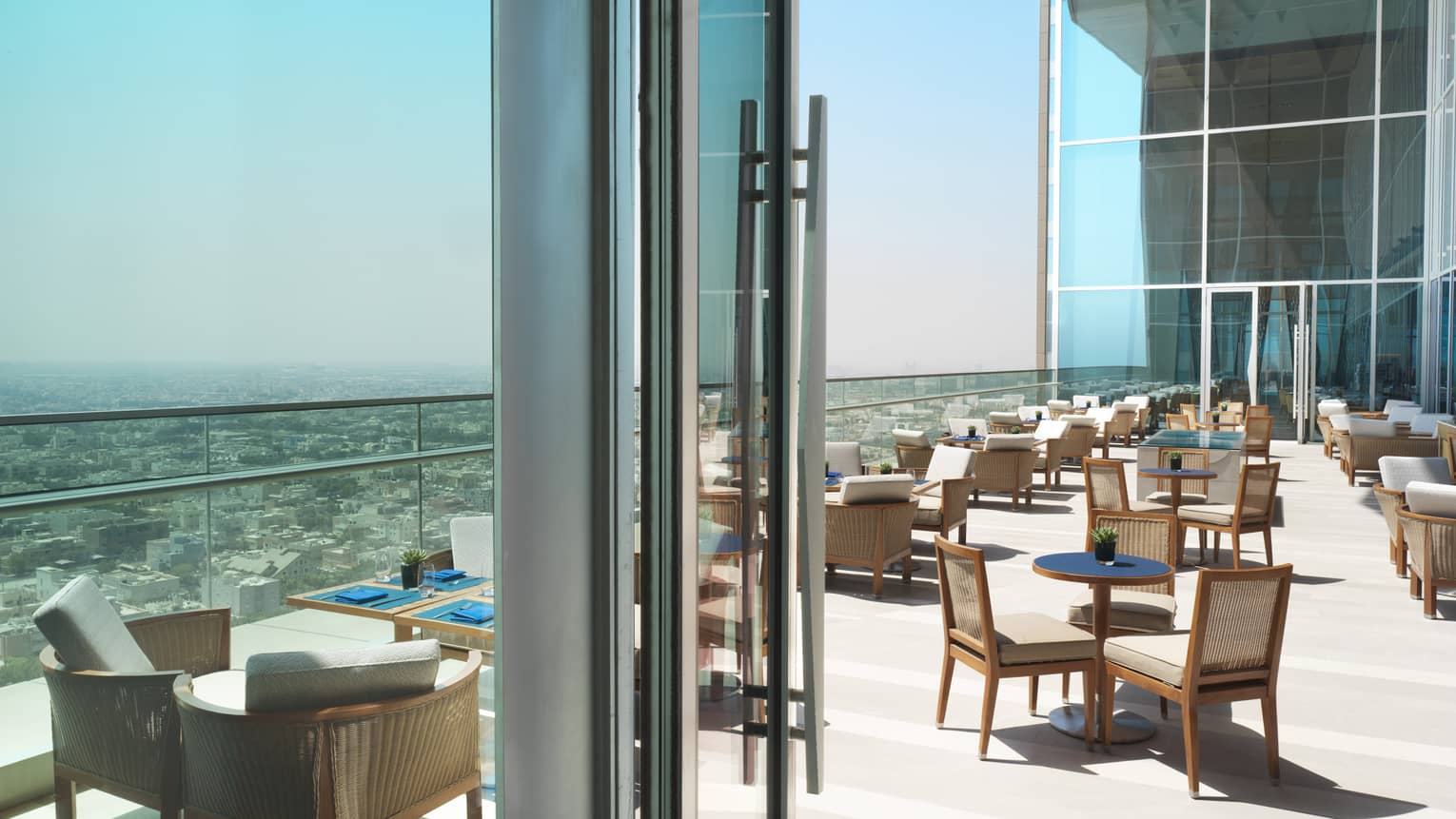 Dining tables and chairs on sunny patio high up on high rise, glass balcony overlooking Kuwait city