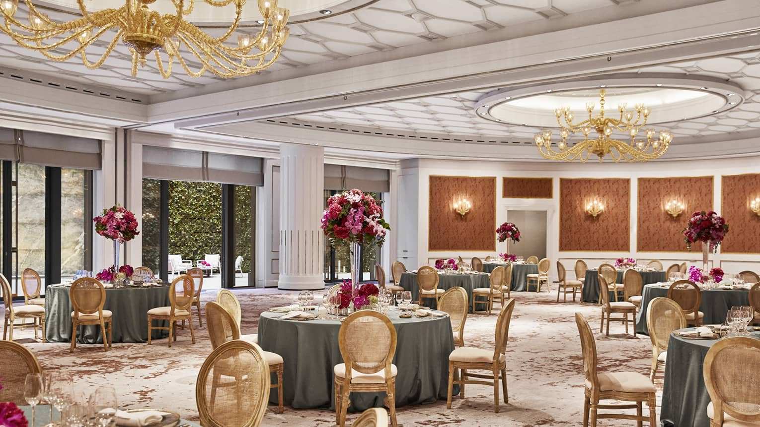 Ballroom with round tables, gold chairs, gold chandeliers, pattern carpeting, wall sconces