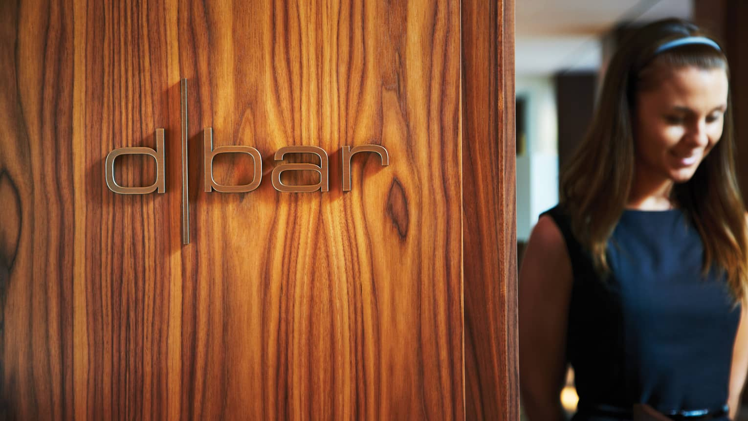 Woman walks through doorway beside wood wall with Dbar sign