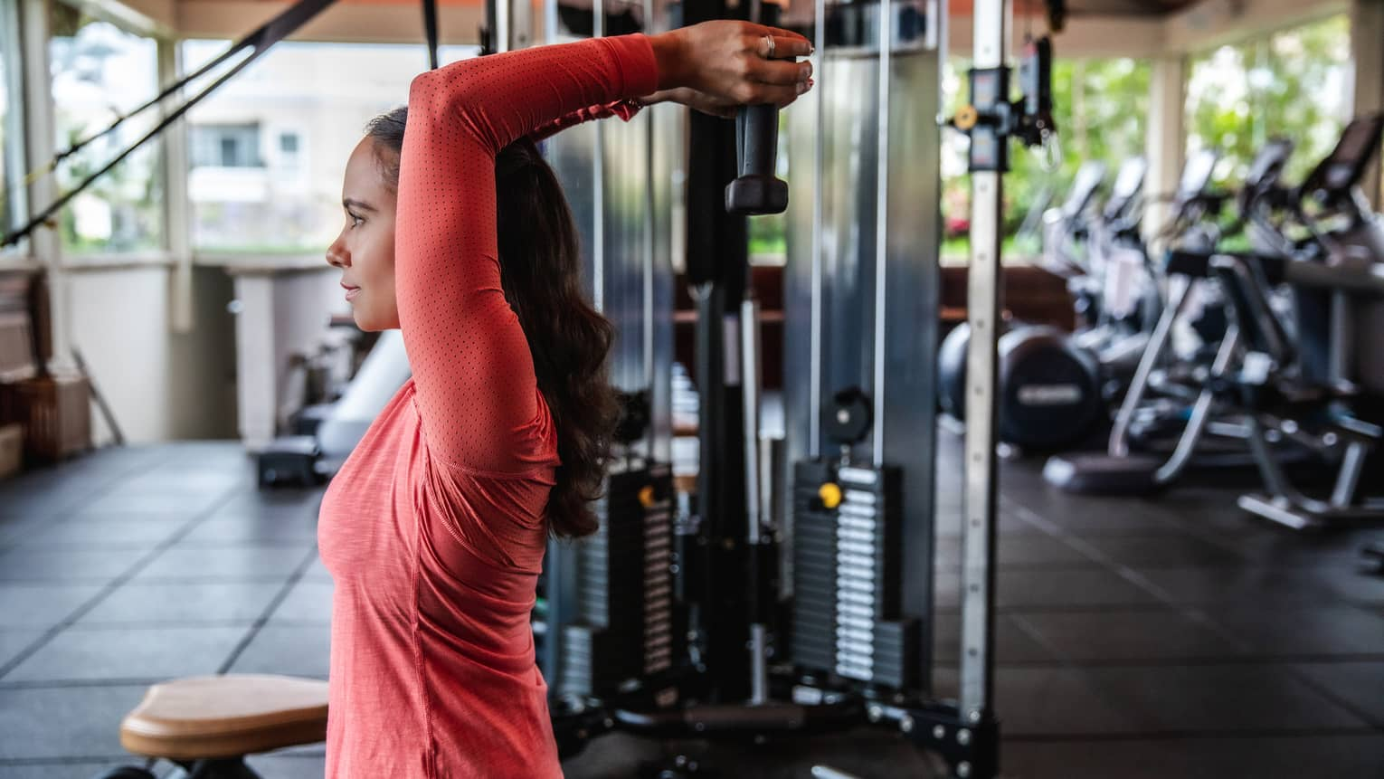 A woman lifts wights above her head at the gym