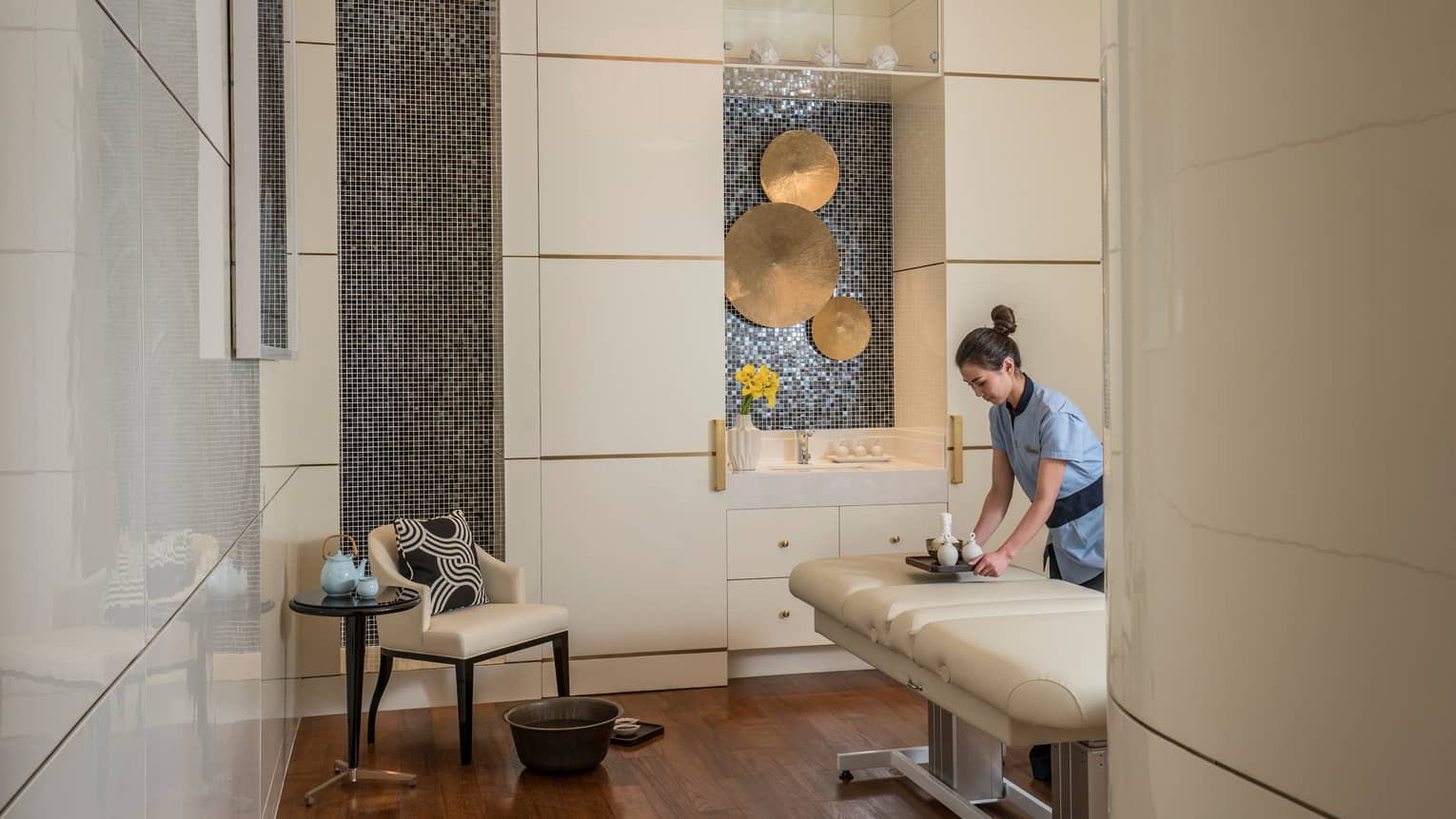 Spa staff sets tray with vases on padded massage table by chair, brass discs on wall