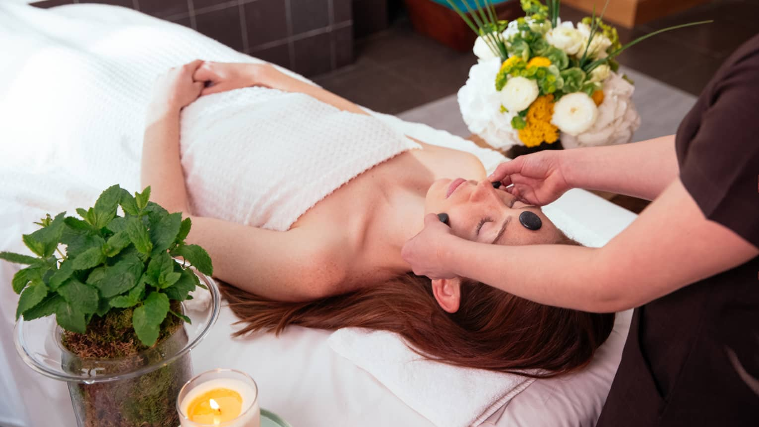 Spa staff places black stones on woman's forehead, cheeks as she lies under white sheet on massage bed
