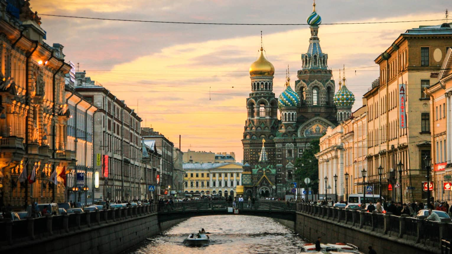 Large cathedral with colourful turrets over canal at sunset