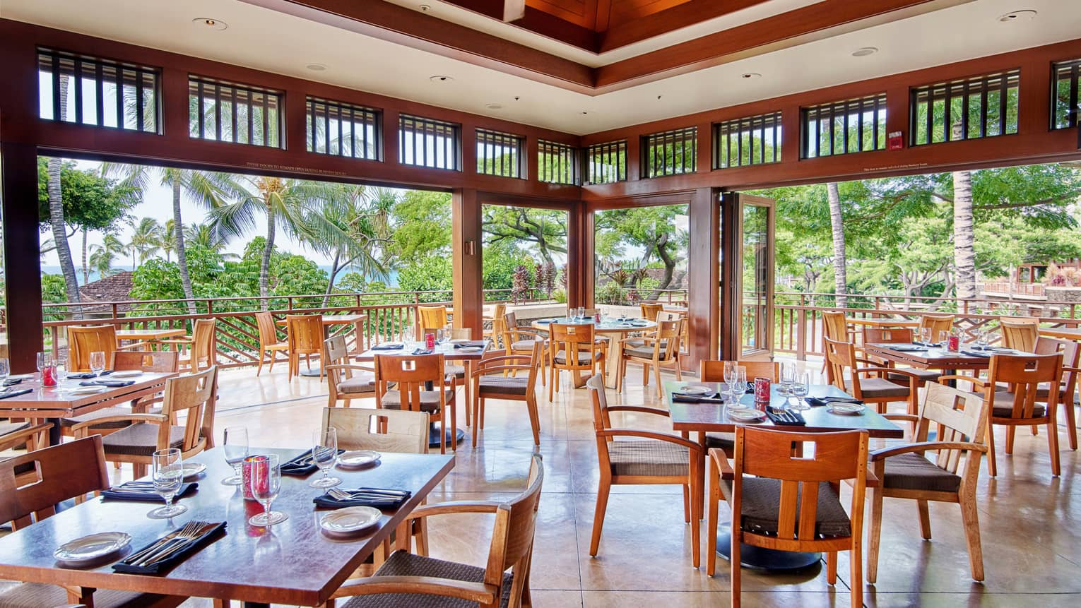 Hualalai Grille open-air dining room under tall wood ceilings