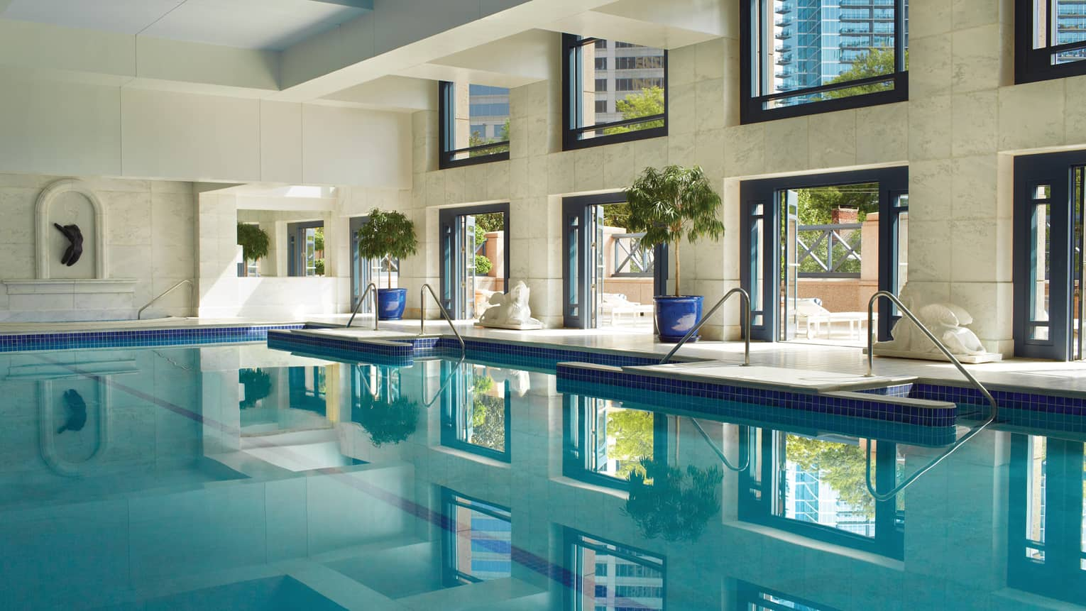 Saltwater lap swimming pool under white marble walls, tall sunny windows