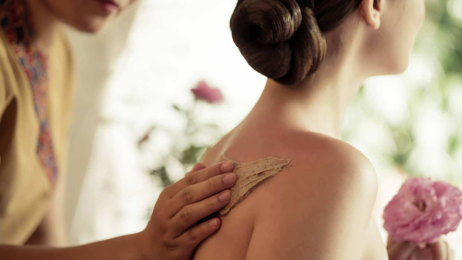 Spa staff rubs thick lotion on woman's bare shoulders as she holds a fresh flower