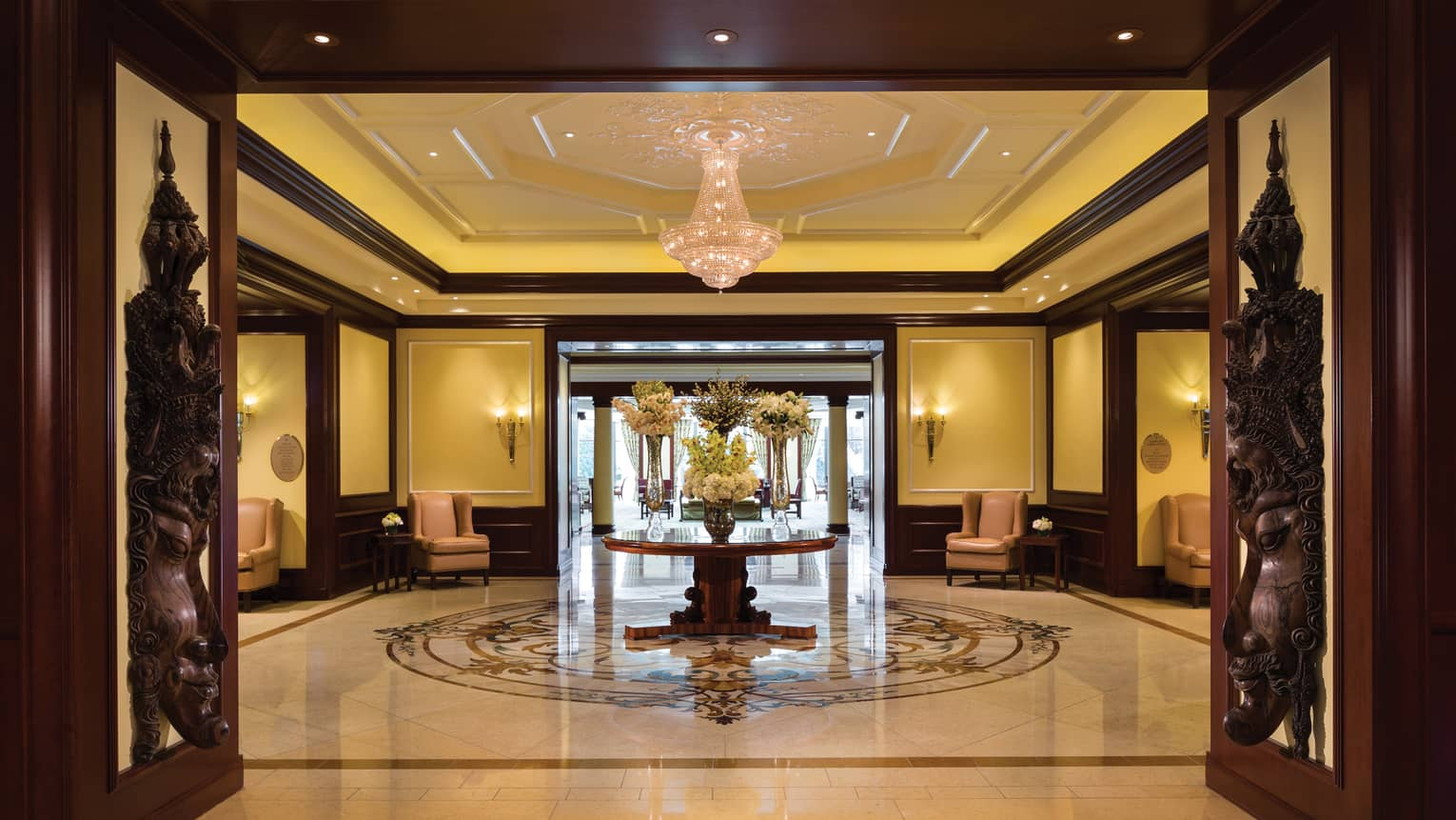 Marble lobby with large flower display, tall open doors with eastern-style wood carvings of faces
