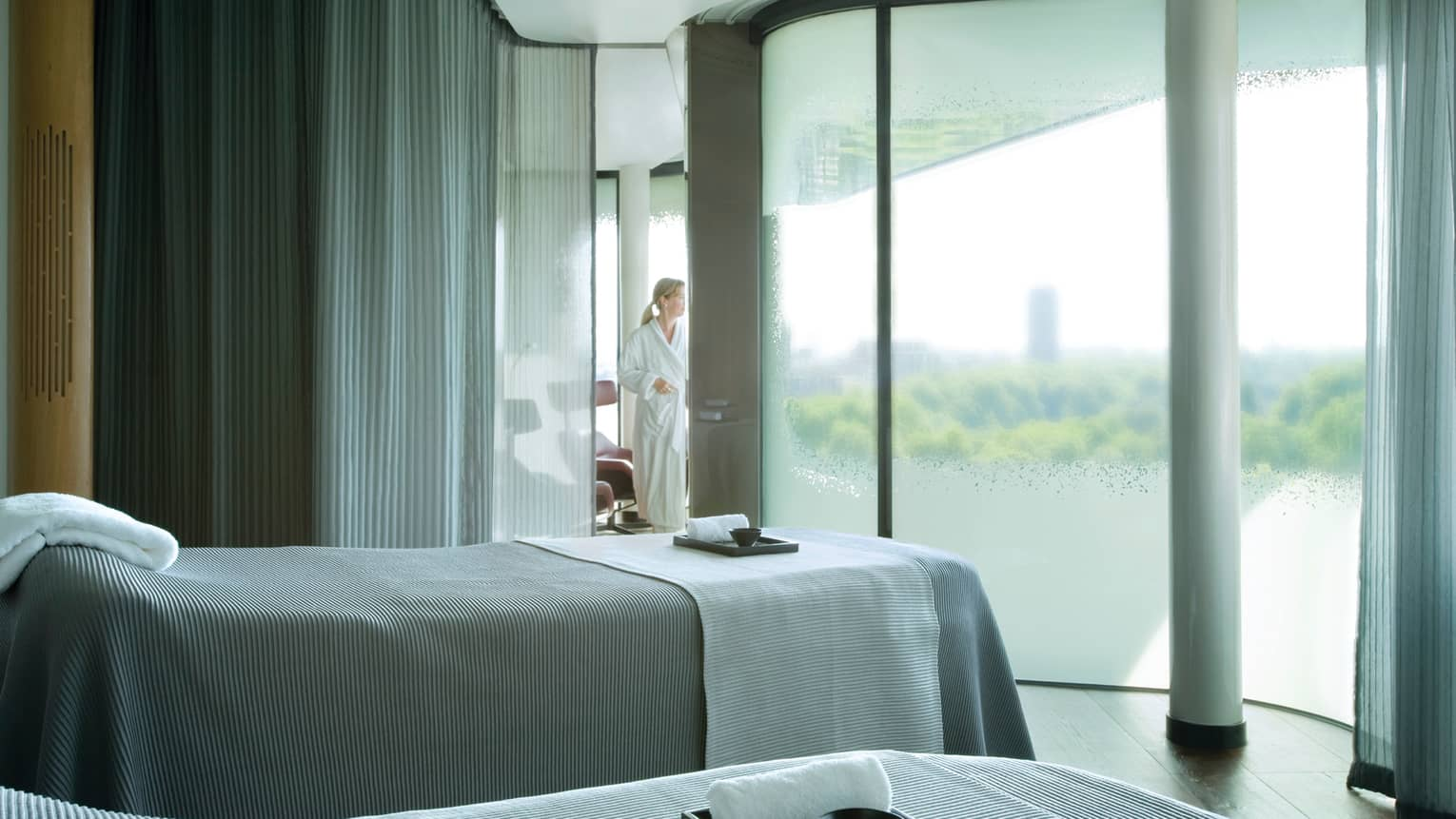 Skyline Spa, woman in white robe behind frosted glass wall, two massage beds