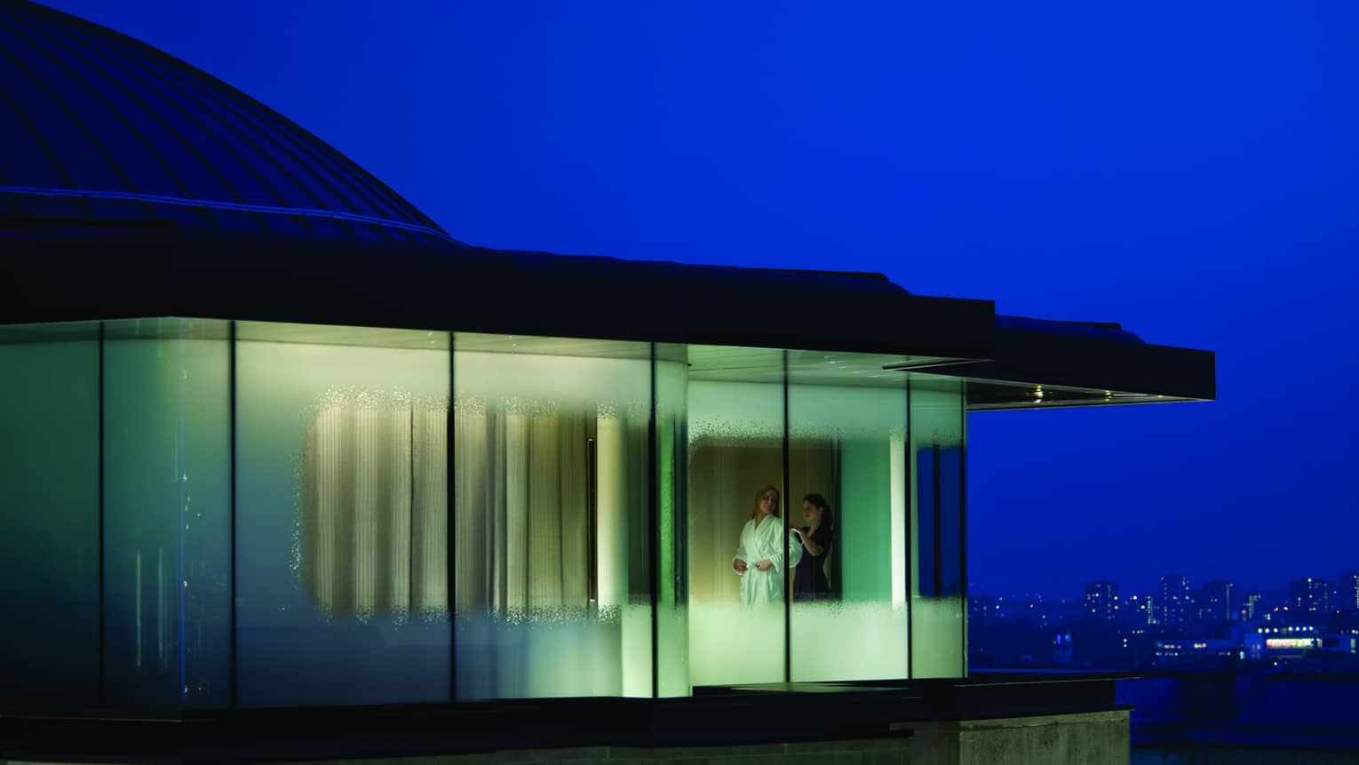 Couple through windows of Spa Sky Suite with green and blue lights at night