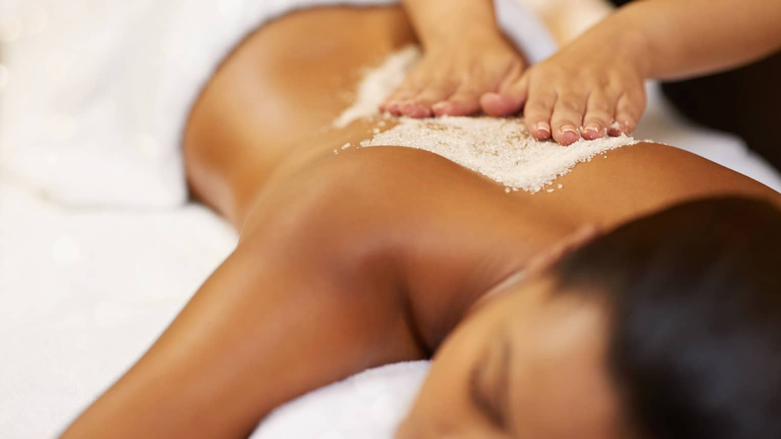 Close-up of hands massaging salt on woman's bare back as she lays with eyes closed on massage table