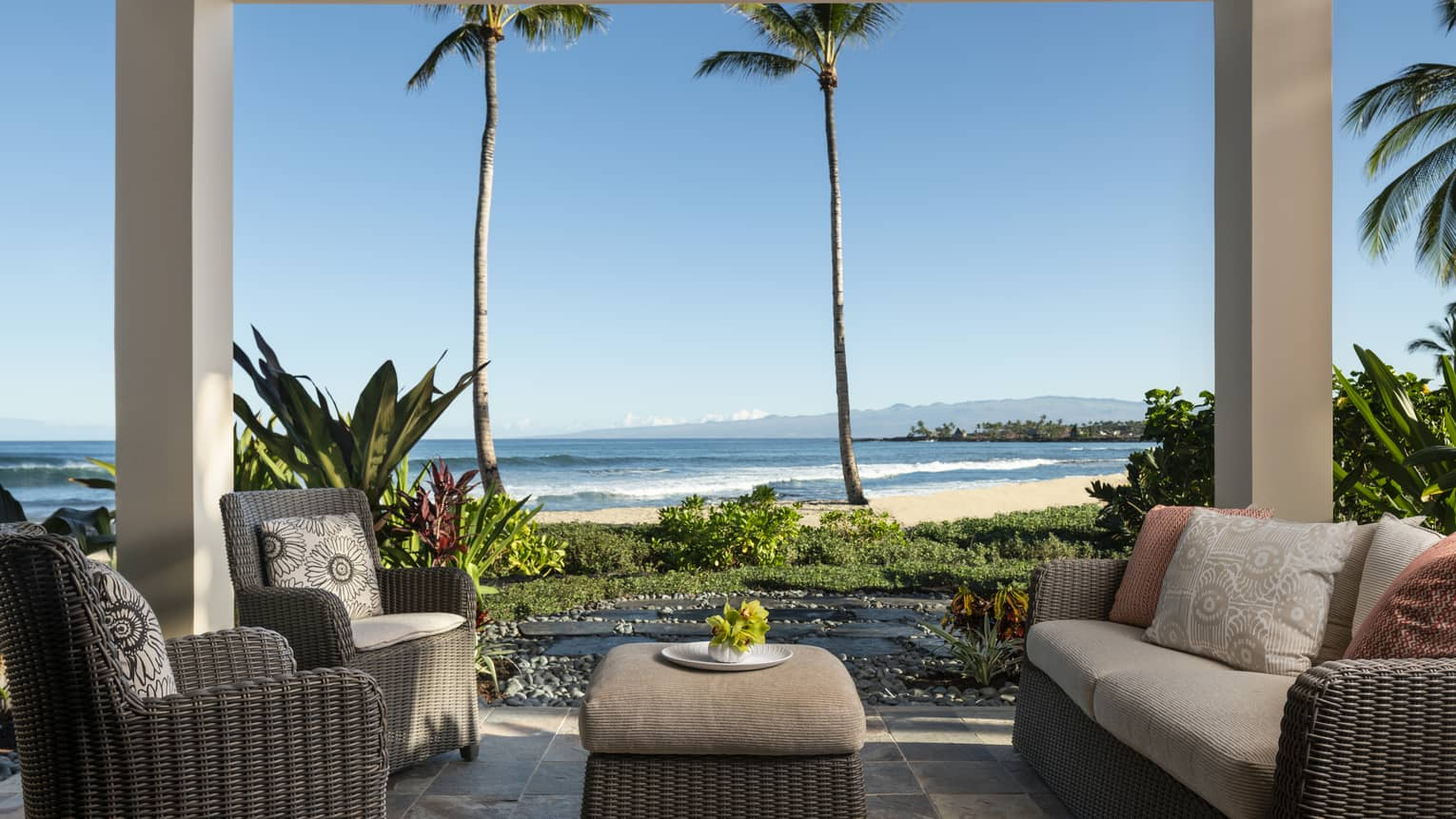 Covered lanai with dark wicker sofa and two matching arm chairs, ottoman, beach view