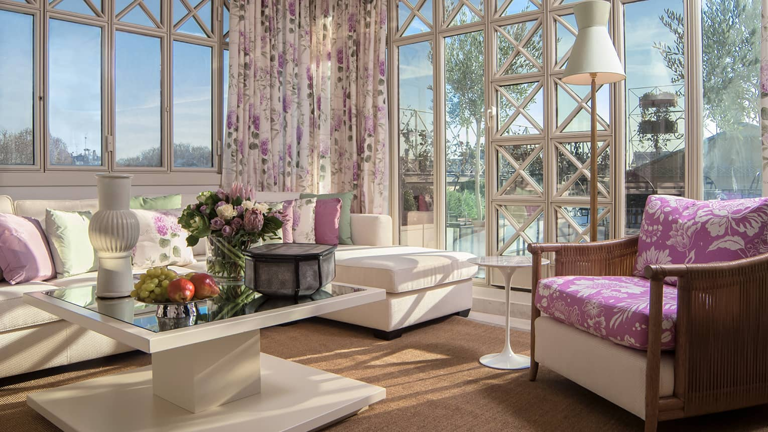 Sunny Presidential Suite, white sofas, lavender floral accent pillows, curtains by glass walls