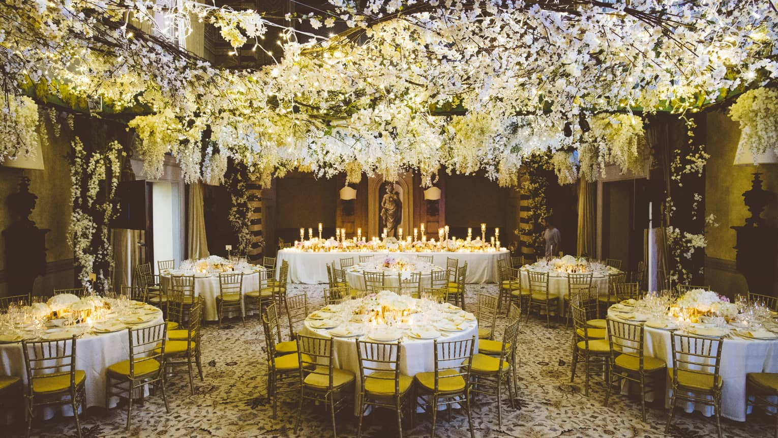 A white floral installation hangs from the ceiling over circular tables are set with white table cloths, brown wooden chairs with yellow seats