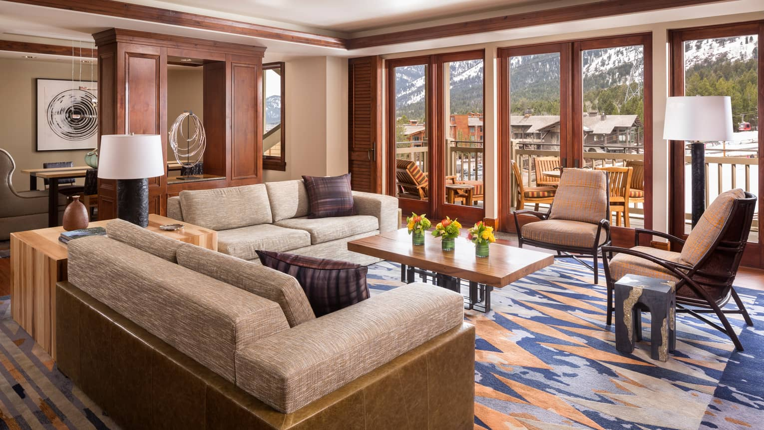 Presidential Suite leather and upholstered sofas, chairs on Midwestern-style rug by glass patio doors