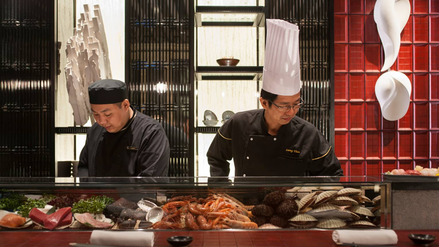 Sushi chefs prepare food behind glass display with fresh seafood, clams, shrimp