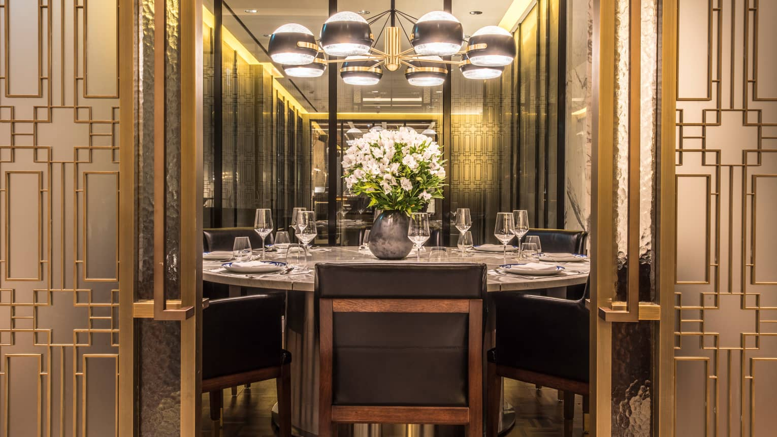 Boccalino large round private dining table under lamp beyond decorative gold screen