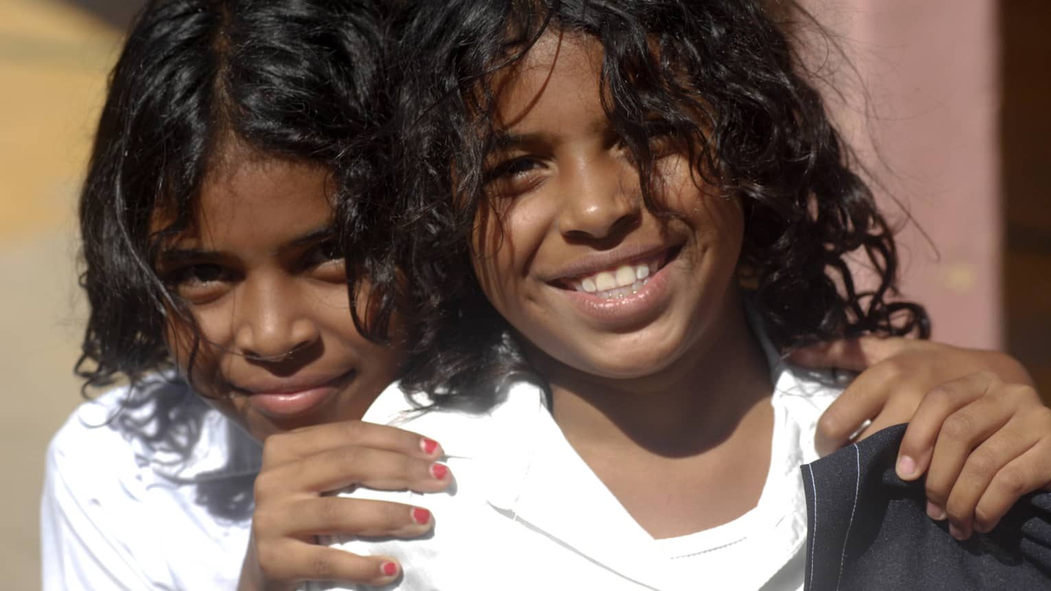 Close-up of two young smiling children, one with hands on the other's shoulders