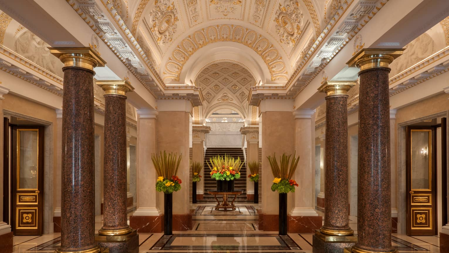 Pillars with gold trim in marble hotel lobby with gilded ceiling, tall vases