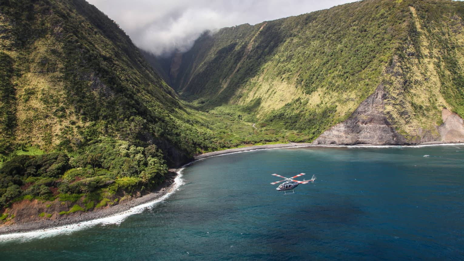 Aerial view of helicopter by sweeping green Oahu volcanic mountains, ocean