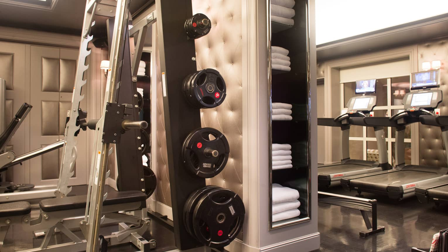 Fitness Centre weight press, barbells by pillar, shelves with white towels