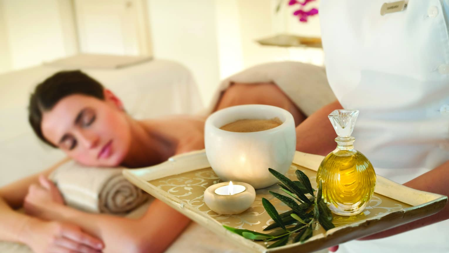 Spa staff holds tray with tealight candle, perfume, marble bowl near woman lying on massage table