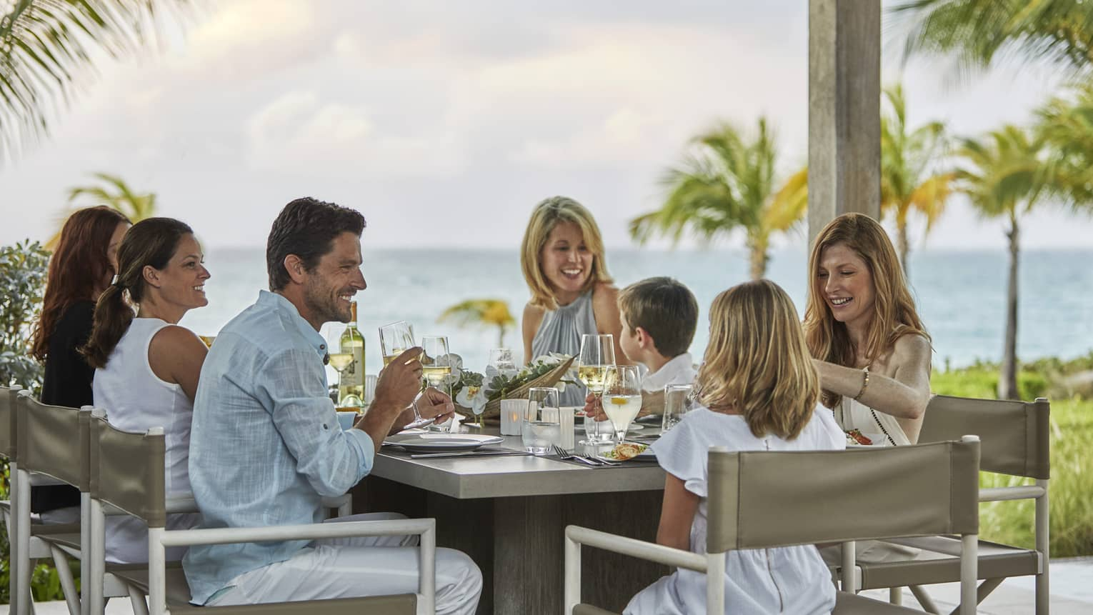 Family of seven enjoys dinner on outdoor table, ocean in background