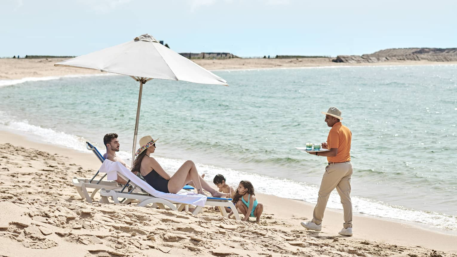 a family lounges on the beach in alexandria while a four seasons staff serves them refreshments