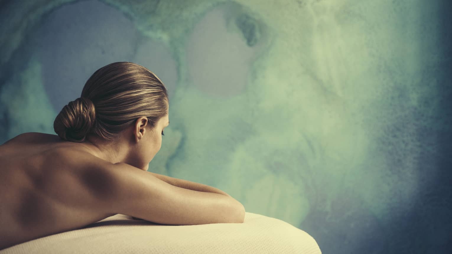 Woman with bare shoulders, hair tied back lies on massage table in front of blue-and-green wall