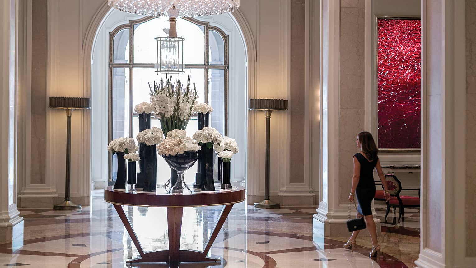 Woman walks by round table with multiple vases with white flowers in marble hotel lobby