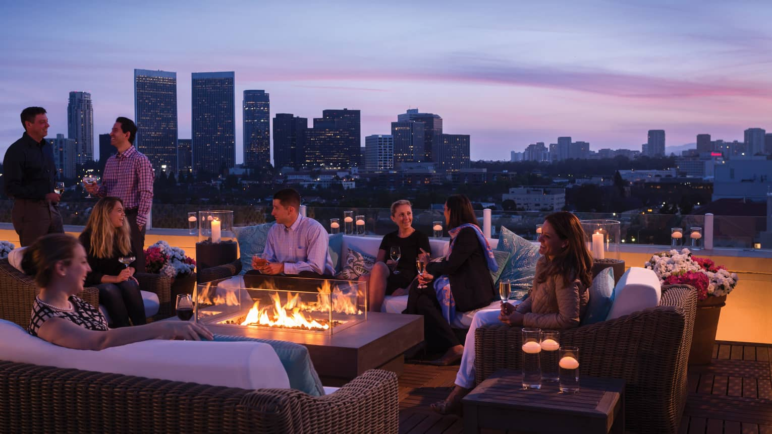 Guests socialize around outdoor fireplace Veranda Suite rooftop terrace, city views at dusk