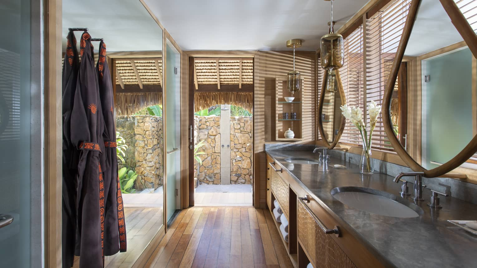 Double vanity sinks in an indoor-outdoor villa bathroom, with teak floors