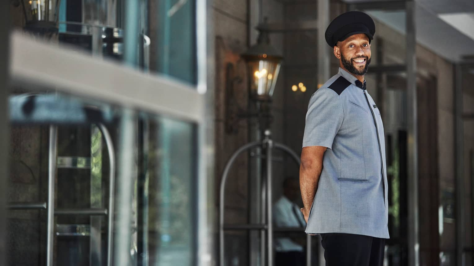 Smiling doorman in short-sleeved grey uniform and black cap with hands behind back stands at lobby door under light