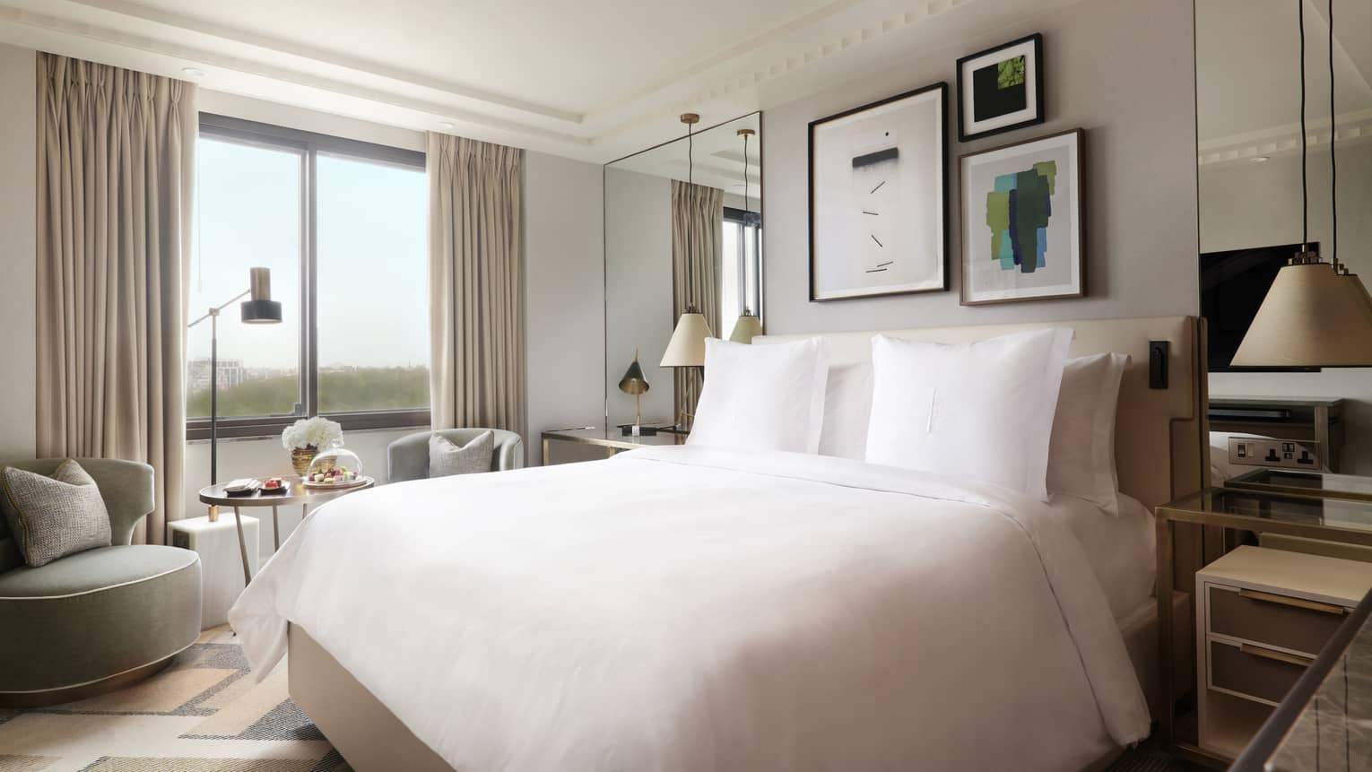 Floor to ceiling windows let light into the Superior King room, furnished with a cream colored modern king bed, modern egg-shaped gray chair, modern prints on the wall