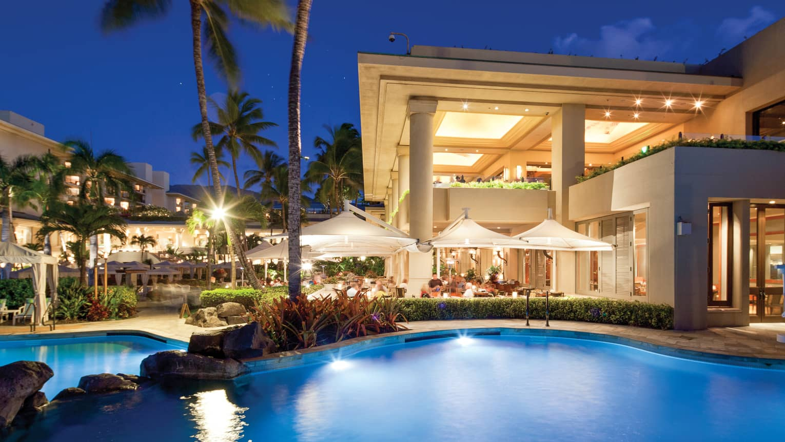 Guests dining beside the Keiki Pool, illuminated at night