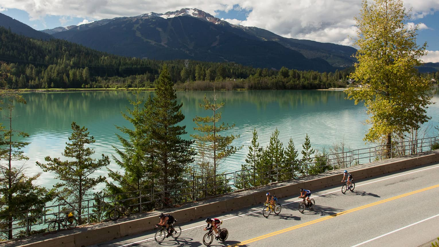 Cyclists bike down road past trees, blue glacier lake under mountains