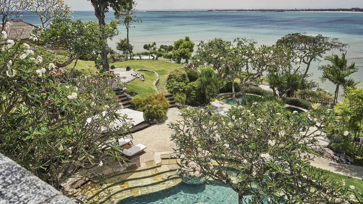 Aerial view through trees of resort stone patio and steps to swimming pool, green lawn, trees and blue ocean