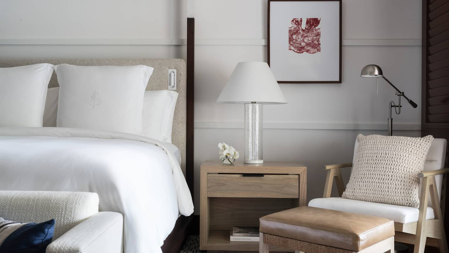 Close-up of white hotel bed, nightstand with white lamp, modern armchair and leather footstool
