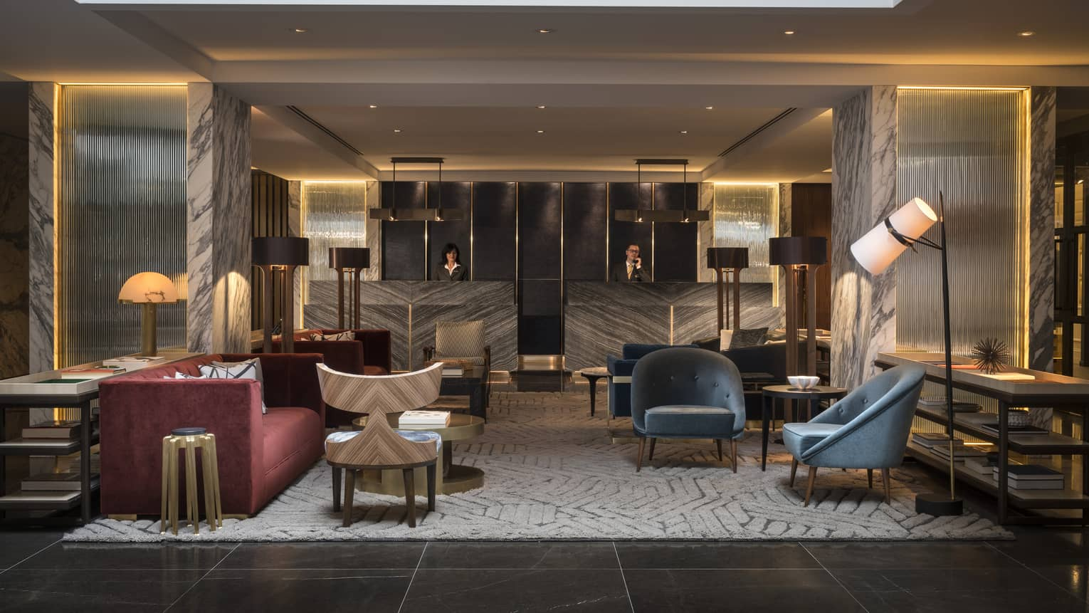 The Lobby of Four Seasons Houston is furnished with two blue velvet arm chairs, a gray and cream abstract rug, a red velvet couch, and an industrial black iron lamp