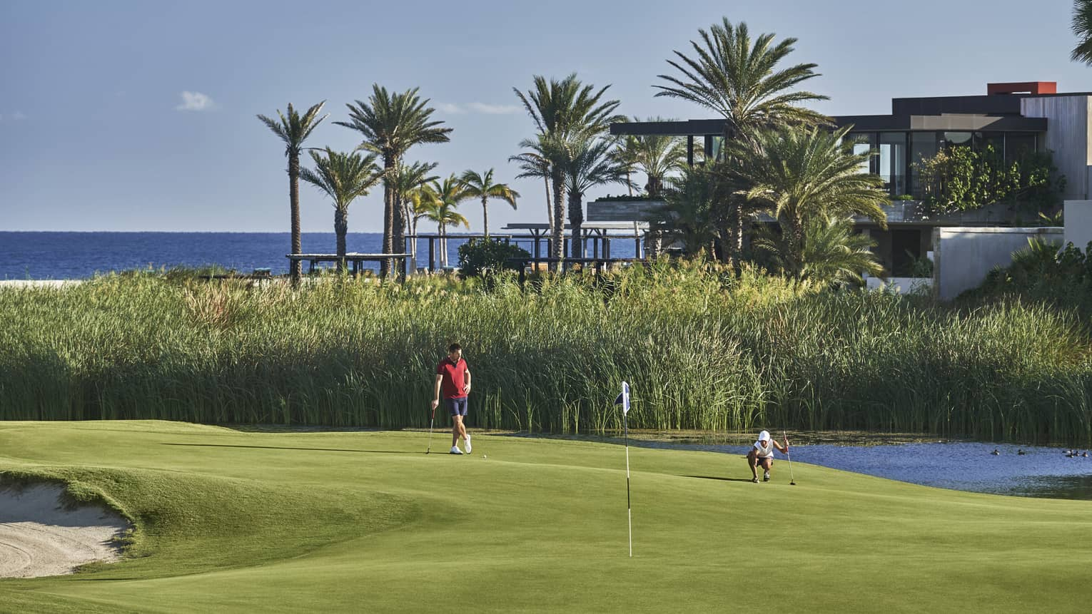 Two golfers enjoy a day on the golf course at four seasons los cabos with palm trees and the ocean in the backgound